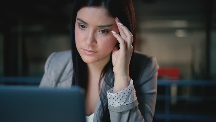 Portrait of a stressed, young brunette business woman holding her face whilst looking at her laptop in a modern office | Shutterstock HD Video #1023427579