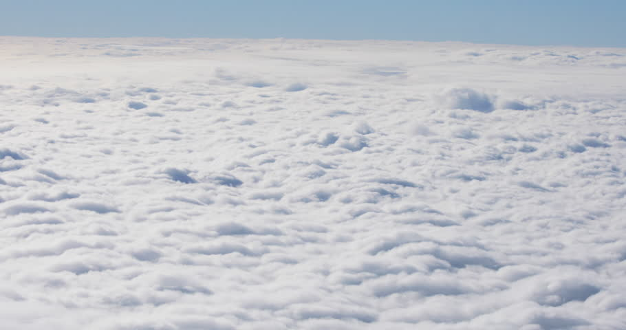 Stunning view of the thick cloud cover under the beautiful blue sky on sunny morning. Flying over the fluffy clouds.