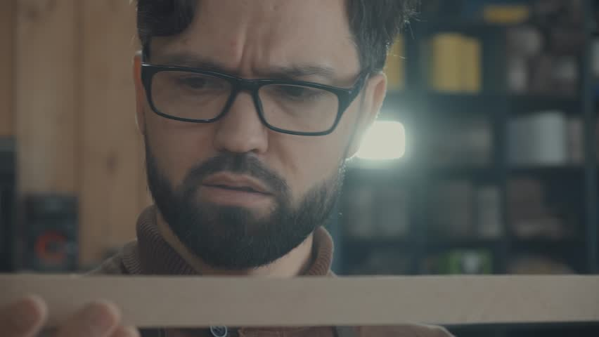 Close-up of a young carpenter's face with a beard and glasses: he holds a wooden piece close to his face and attentively checks the quality. Concept carpenter, work in the workshop, craft | Shutterstock HD Video #1023473299