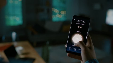 Close Up Shot of a Smartphone with Active Smart Home Application. Person is Tapping the Screen and Light is Being Turned On in the Room. It's Cozy Evening in the Apartment.