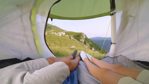 SLOW MOTION POV: Young hikers wiggling their toes while relaxing in their tent and observing the stunning green mountains in Slovenia. Playful couple relaxing in tent during their camping adventure.