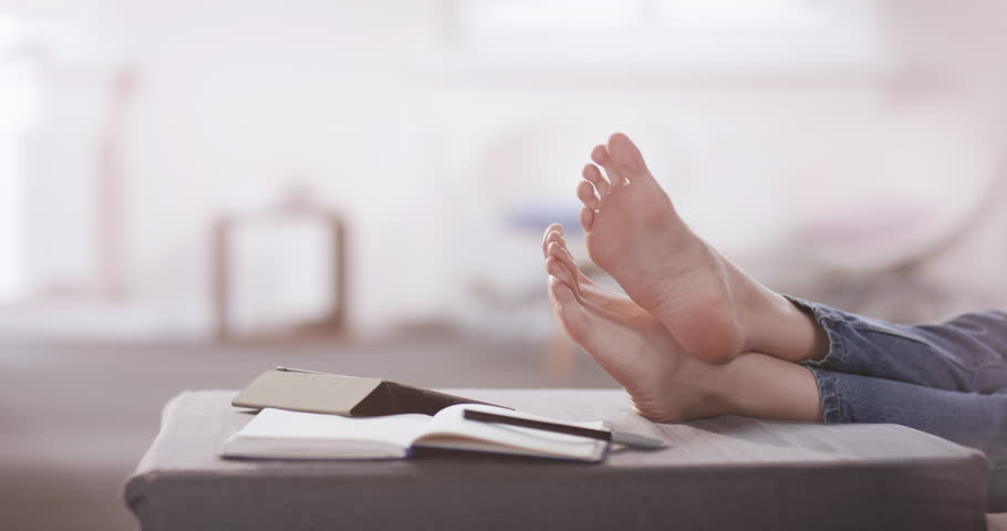 Young women relaxing barefoot in her home office | Shutterstock HD Video #1023582469