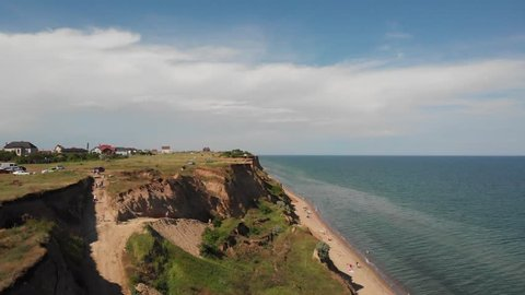 Aerial drone view of landslide ragged sea shore with sandy beach, blue water, green scenery on a clear sunny summer day