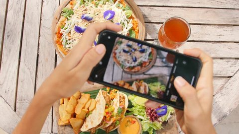 Young Blogger Woman Taking Photo of Mexican Food Using Mobile Phone in Vegan Restaurant. 4K Slowmotion Flatlay Food Porn Concept on Wooden Table View From Above. Bali, Indonesia.