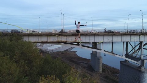 Equilibrists walk a rope tied to a bridge