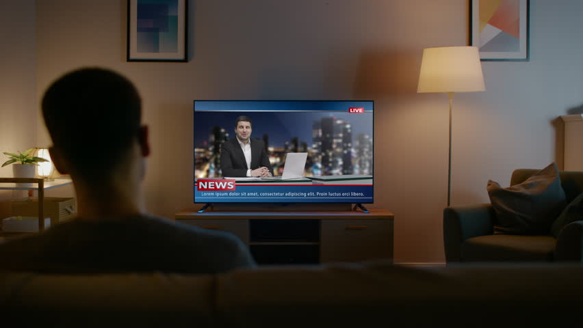 Young Man in Glasses is Sitting on a Sofa and Watching TV with Live News. It's Evening and Room at Home Has Working Lamps. | Shutterstock HD Video #1023697489