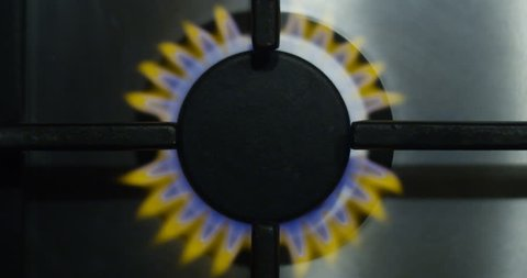 Gas Burning Stove with Yellow and Blue Fire Flame in Kitchen Hob with Stainless Steel Surface Top View Shot on Red