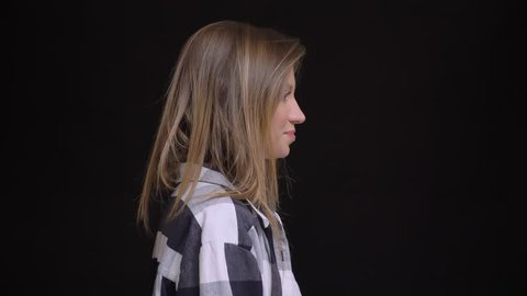 Portrait in profile of young caucasian long-haired girl in plaid shirt turns to camera and watches joyfully into it on black background.