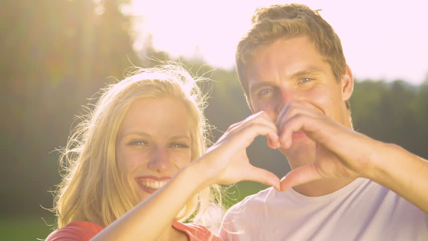 PORTRAIT SUN FLARE Adorable couple makes a heart shape with fingers during a fun outdoor date in the countryside. Golden sunbeams shine on smiling young man and woman creating a heart shape with hands
