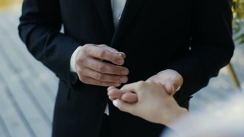 The groom puts the wedding ring on finger of the bride and kisses her hand. The bride and groom exchange wedding rings.