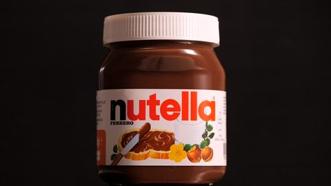 BOLOGNA, ITALY - FEBRUARY, 2019: Nutella jar against black background. Nutella is manufactured by the Italian company Ferrero and was first introduced in 1965. Illustrative editorial.