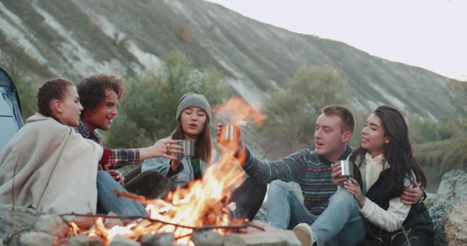 Campfire group of friends sitting down and drinking tea or some hot drinks , from metallic cups , they are very charismatic. | Shutterstock HD Video #1023837409