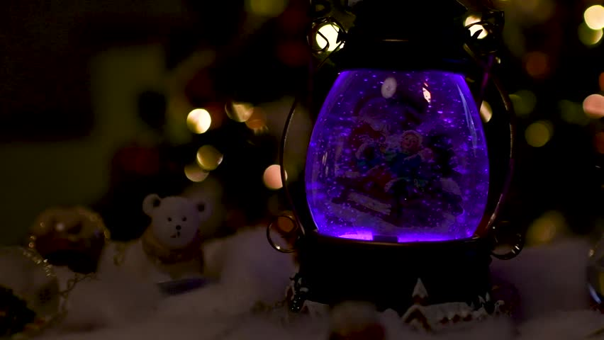 Beautiful Christmas decoration with snow globes and others ornamentations on a table and lights blurred in the background. Panoramic plane shift