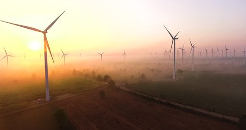Aerial view of Wind turbines Energy sunrise in forest with fog. Production by of drone footage 4k aerial shot on sunrise. with environment friendly renewable energy concept.