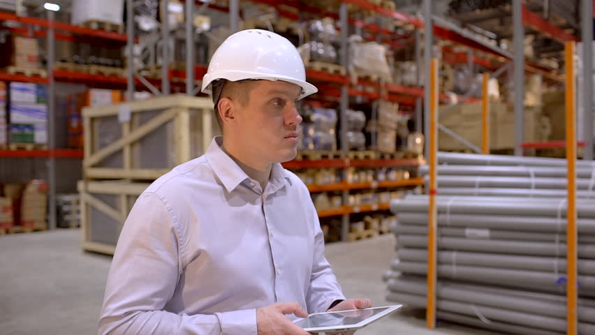 Employee male warehouse worker engineer man in hard hat working at construction site warehouse, walking in logistics center factory, engineer using tablet computer, architect businessman man indoors | Shutterstock HD Video #1023949859