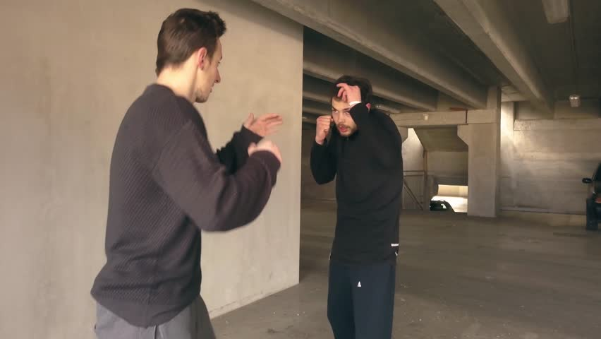 Closeup of men fighting in a parking garage. Man being attacked in a car park fights back by punching and kicking the attacker. Actors in a staged fight scene. #1024003649