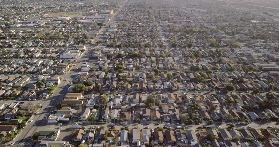 Downtown city neighborhoods helicopter wide shot POV aerial view of suburban area streets, homes, and cars in Los Angeles, California United States