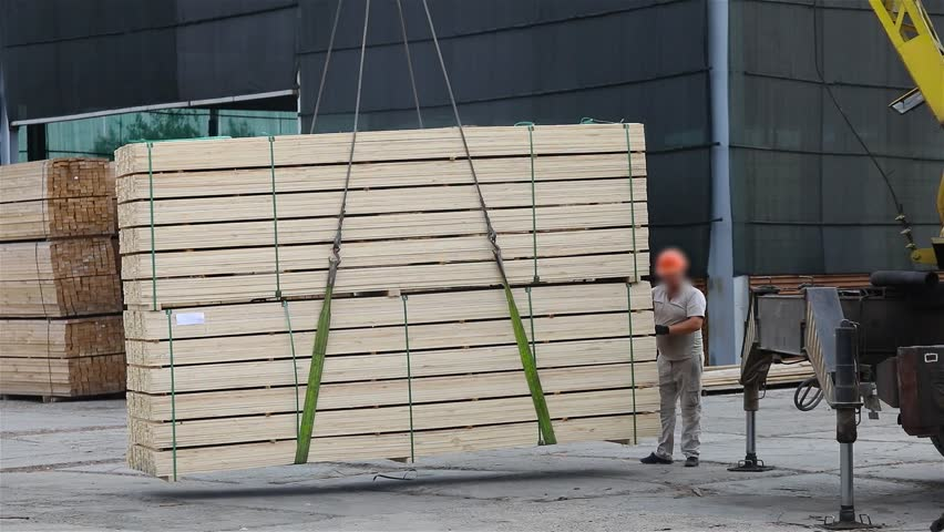 Men load a wooden beam into the car, loading the cargo into the car using a crane