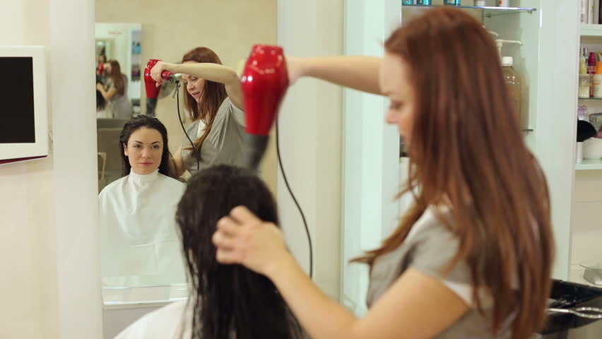 Beautician blow drying woman's hair after giving a new haircut at parlor. Professional hairdresser drying hair of a young girl.