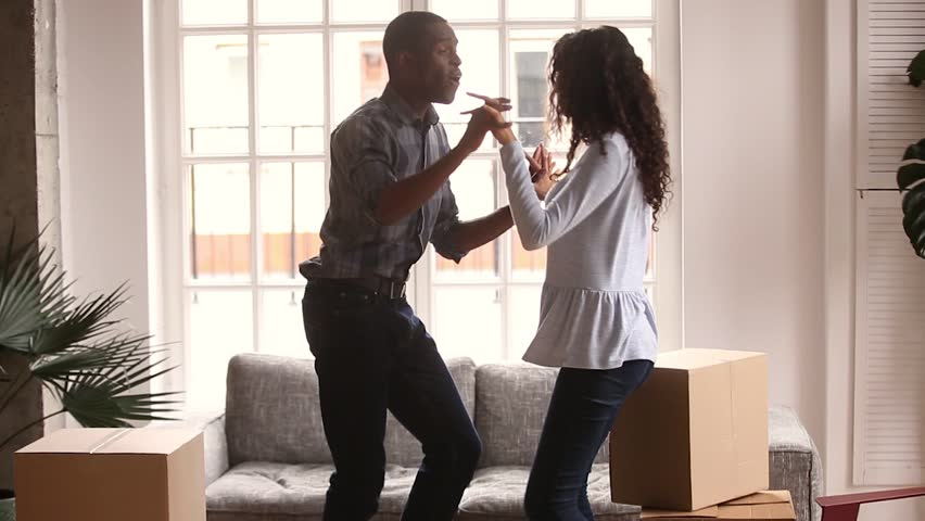 Happy african american first time home buyers couple dancing laughing having fun celebrate relocation buy house in living room with boxes, cheerful black family enjoy moving to music in new apartment