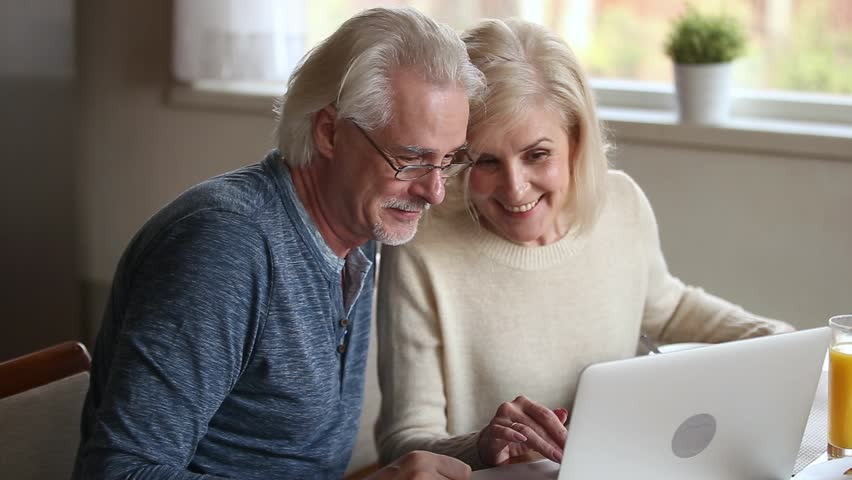 Happy old middle aged couple using laptop talking together doing online shopping, senior mature retired family reading discussing internet computer news, choosing travel offer on website at home