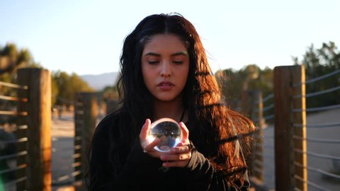 A beautiful woman with magic powers looking serious and staring into her  magical crystal ball while casting an enchanting spell to predict the  future
