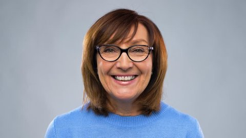 communication, age and people concept - happy senior woman in glasses having video chat or interview over grey background