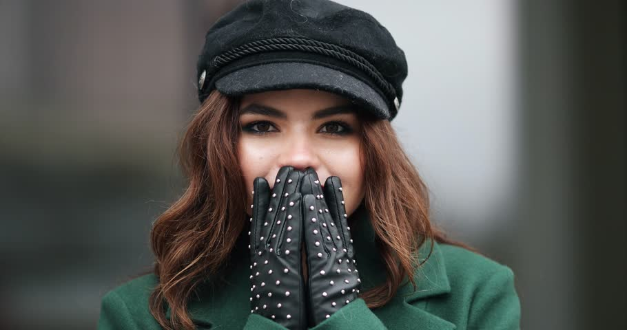 Portrait of charming smiling brunette with red lips wearing trendy black cap and green coat with dragonfly brooch. She is twisting and smiling. | Shutterstock HD Video #1024110059
