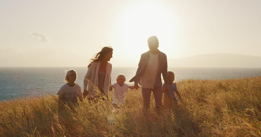 Happy smiling family swinging child into the air in golden fields by the ocean at sunset | Shutterstock HD Video #1024117919