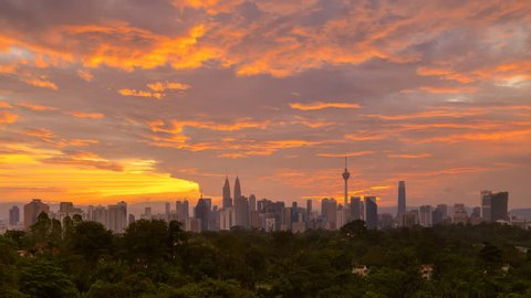 Time lapse: Silhouette of Kuala Lumpur city view during dawn overlooking the city skyline from afar with lushes green in the foreground. Federal Territory, Malaysia.