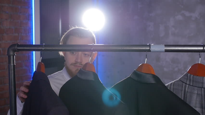 Shopping and fashion concept - Young bearded man choosing and trying jacket on in mall or clothing store | Shutterstock HD Video #1024153319