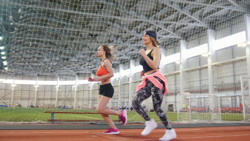 Two young athletic women running in sports arena indoors #1024169189