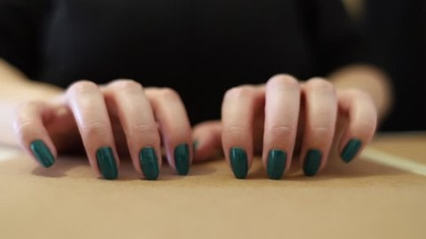 Female long nails tapping on hard surface. Fast and slow handements. Green painted Nails