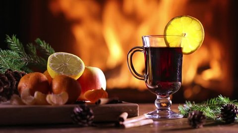 A glass of mulled wine (gluhwein) and a plate of fruit on the background of a burning fireplace