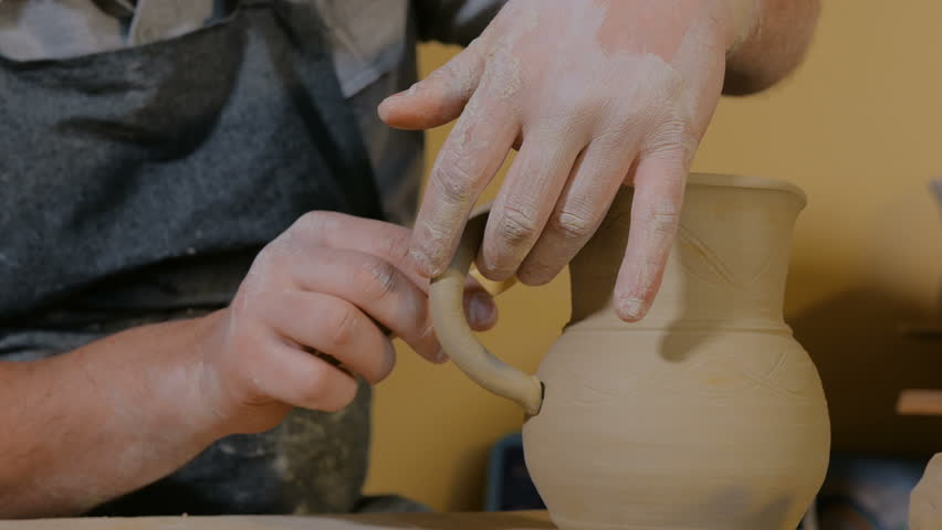 Professional male potter making ceramic jug with handle in workshop, studio. Handmade, small business, crafting work concept | Shutterstock HD Video #1024308269