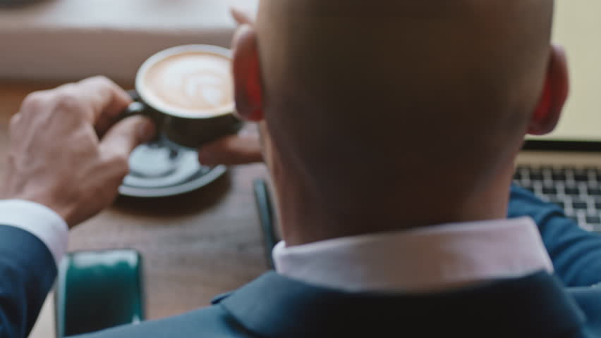Businessman using digital laptop computer in cafe drinking coffee working browsing emails networking online enjoying internet connection | Shutterstock HD Video #1024313159