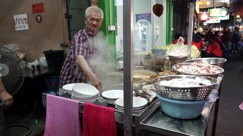 Bangkok, Thailand  - February 5 2019: An old man working at Chinese noodle shop in China Town, Bangkok. Street food in China Town is a popular tourist destinations for both locals and foreigners.