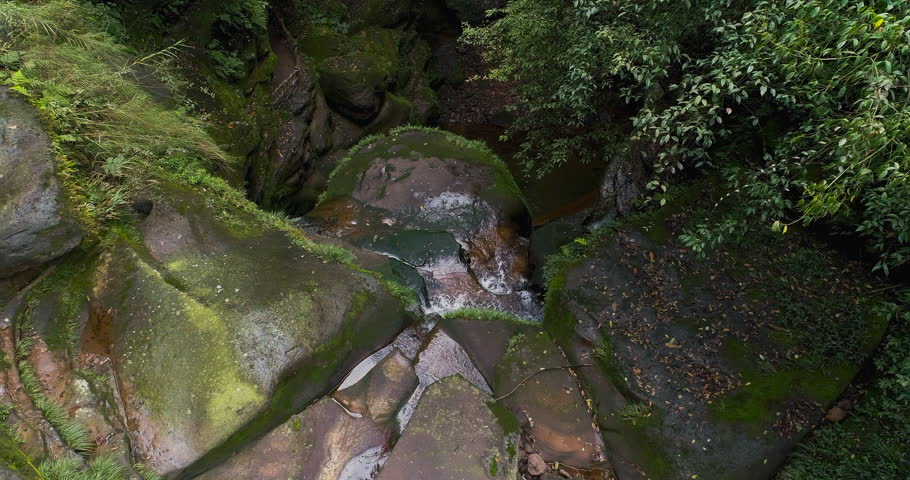 Aerial above view looking down through trees of a stream waterfall flowing in the mountain valley, 4k nature landscape drone footage.   Shutterstock HD Video #1024383089