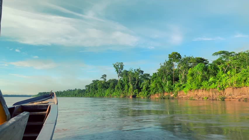 Slow motion shot of a wooden speed boat traveling on Amazon river. Amazon, jungle, rainforest. Peru.
