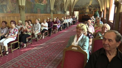 OLOMOUC, CZECH REPUBLIC, APRIL 15, 2018: Knight's Hall in the town city hall of Olomouc, people applause and clapping, old people retirees sitting on chairs, gothic vaulted ceiling, ceremonial