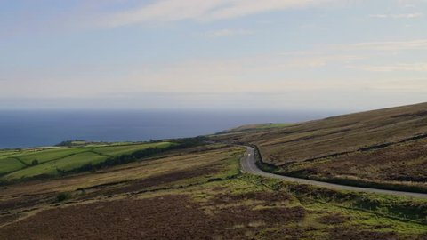 Aerial: Motorbike on the Isle of Man TT course. Coming out of Ramsey and at the start of the mountain section. 4k