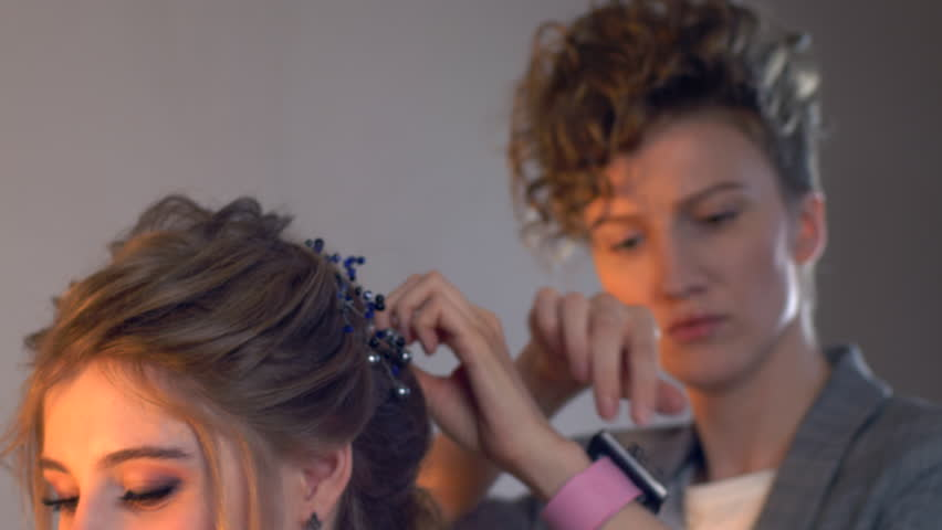 Makeup artist and hairdresser are preparing bride before wedding. Hairdresser-stylist with short stylish hairstyle applies makeup, makes false eyelashes, paints lips, curls girl, spectacular lighting #1024556009
