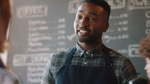 young african american barista man serving customers in cafe using smart watch making contactless payment buying coffee spending money enjoying service