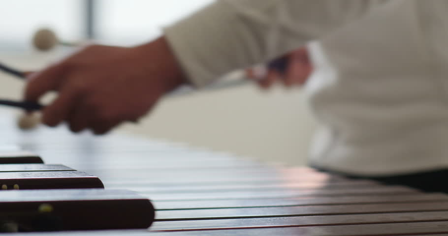 very cinematic short focal depth shot of musician percussionist sticks playing marimba music on his instrument. fast drumsticks hitting wooden instrument. blurred background and beautiful bokeh
