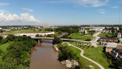 Aerial Drone Footage Traveling down the Buffalo Bayou and over a Bridge in the City of Houston