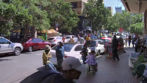 Johannesburg, South Africa, 23 February - 2019: View down city street in fashionable area with people walking in street.