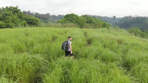Backpack tourist walks through the field in Ubud. Aerial view.