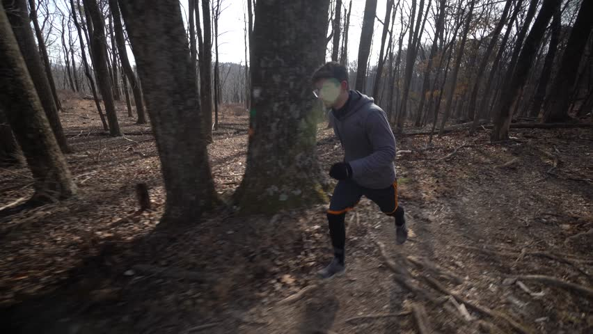 Camera follows beside a trail runner as he runs to the right down a forest trail. | Shutterstock HD Video #1024711259