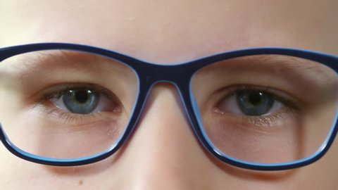 Extreme close up shot of young blue eyed Caucasian boy putting on glasses and looking at camera