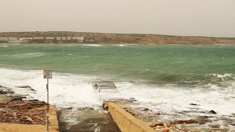 Mellie?a, mellieha / Malta - 04 14 2018: Mellieha, Malta, April 14 2018 - Incoming tide, rough sea waves against slipway, Slipway sign at Ghadira bay, Mellieha, Malta